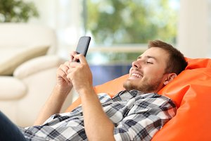 Relaxed man using a smart phone