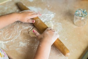 Children's hands holding rolling pin