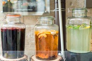 glass jars filled juices on wooden stumps