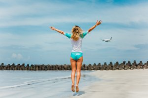 girl on the beach. plane in the sky