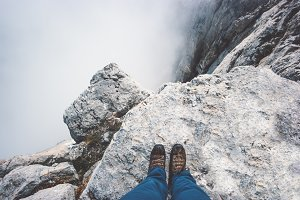 Feet boots on rocky mountain cliff