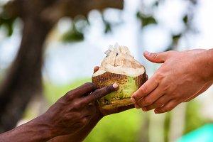Dark-skinned hand  white man, white and black man, coconut in ha