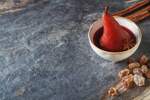 Pears poached in red wine, with star anise on a white plate. Dark background.