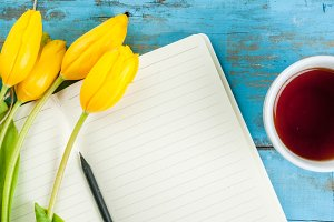 Tea mug with tulips and notebook