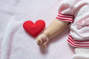 Red heart with baby hand