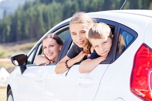 Happy young mom and her children sitting in a car