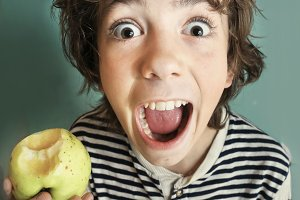 boy with strong white teeth bite apple