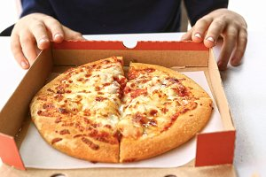 pizza in cardboard box with kids hands