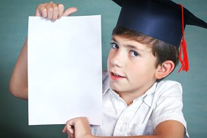 boy in graduation cap whith white paper sheet