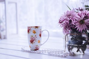 Pink flowers with cup of tea near the window