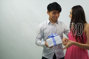 Young man presents gift box to girl on a white background