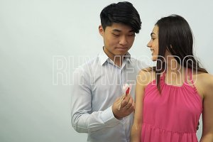 Asian guy presents Valentine card with a wedding ring to young girl on a white background