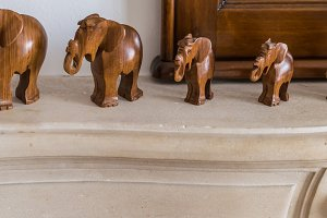 Carved wooden elephants on pedestal