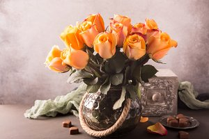 Bouquet of blossoming yellow roses in vintage vase.