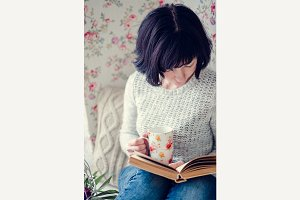 Beautiful woman drinking hot tea and reading a book