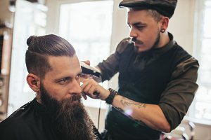 Young bearded man getting haircut