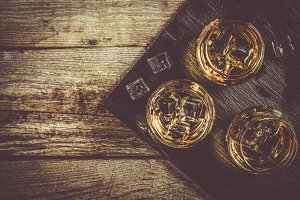 Whiskey in glasses on rustic wood
