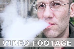 Man exhaling e-cigarette smoke cloud from mouth