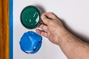 Hand holding green paint can cover