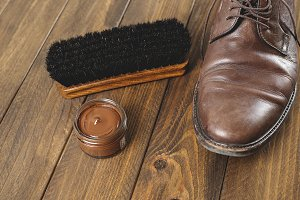 Shoe cleaning product and brush next to a dirty brown shoe. Horizontal shoot.