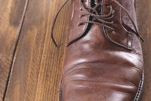 Used and dirty brown shoe on brown wooden table. Vertical shoot.