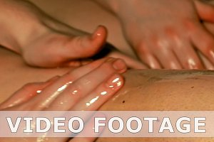 Woman gets four hands oil massage on her legs