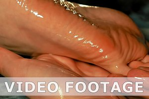 Woman gets four hands oil massage on her foots