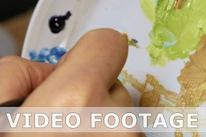 Graphic artist mixing oils color paints in palette