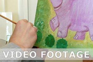 Female artist paints picture artwork in art studio
