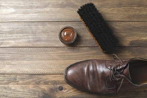 Dirty brown shoe next to brush and cream on wooden table. Horizontal shoot.