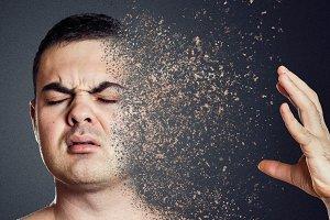 Depressive man dissolving his face into pieces. Mental health concept.