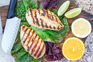 Grilled chicken breast in citrus marinade on salad leaves and wooden cutting board, horizontal, top view