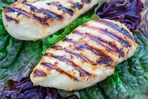 Grilled chicken breast in citrus marinade on salad leaves and wooden cutting board, horizontal, closeup