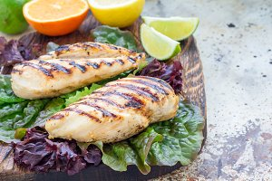 Grilled chicken breast in citrus marinade on salad leaves and wooden cutting board, horizontal, copy space