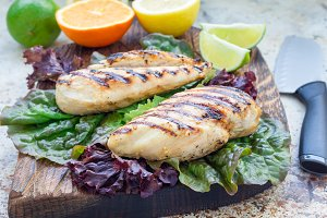 Grilled chicken breast in citrus marinade on salad leaves and wooden cutting board, horizontal
