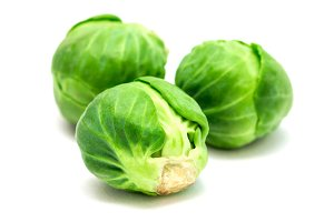 Three fresh brussels sprouts isolated on white background