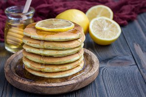 Healthy homemade lemon and chia seed pancakes served with honey, horizontal, copy space