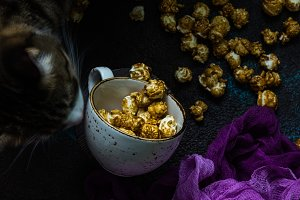 Homemade Golden Caramel Popcorn in a cup and cat