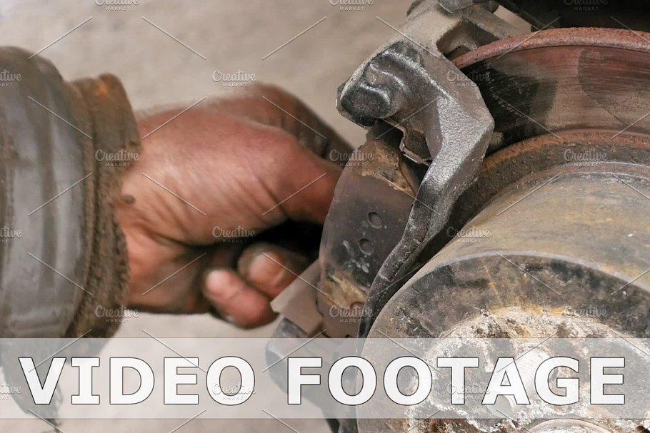 Auto mechanic working on brakes in car repair shop