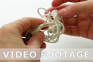 Woman untangles tangled earbuds or earphone knot