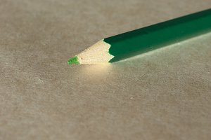 Green pencil over paper