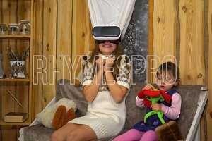 little Girl with Sister Wearing VR Headset at Home