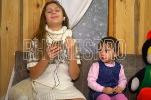 Teen girl with little sister listening music from a smartphone at home