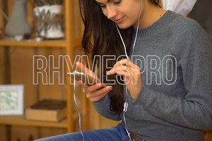 Young girl with headphones listening music from a smartphone and sings at home