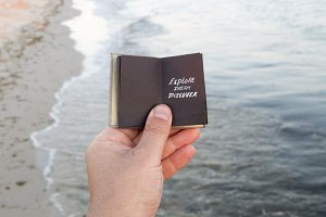 Visit Beaches idea. Hand holding a book with the inscription.