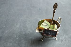 Healthy dinner ideas tag and Kiwi fruit on silver bowl. Food background. Vintage composition.