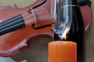 Champagne, violin and burning candle