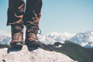 Feet trekking boots on rocky cliff