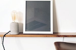White frame stand on a wooden shelf