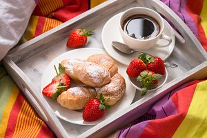 Mini croissants with berries and coffee in a bed.